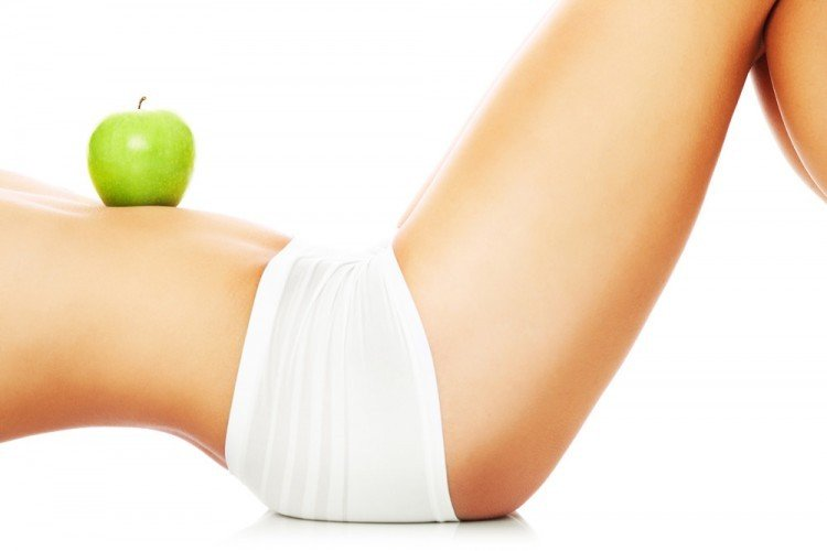 A fit woman with an apple on her tummy