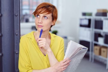 woman with pen and paper thinking