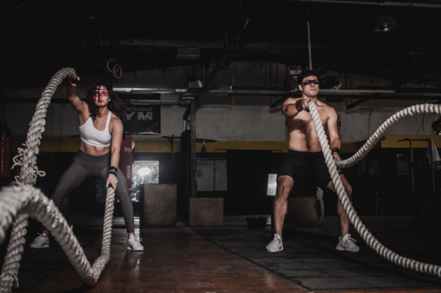 male and female working out with ropes in gym