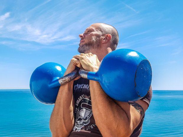 man on beach with kettlebells