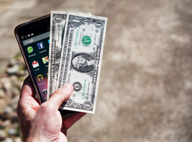 man holding cell phone and dollar notes