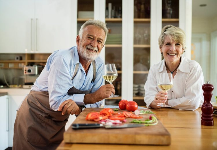 man and woman in kitchen enjoying wine