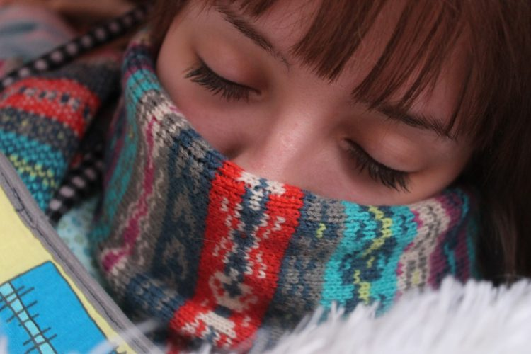 woman with scarf around face sleeping