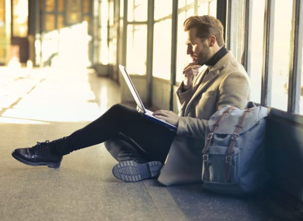 man sitting on floor airport with laptop